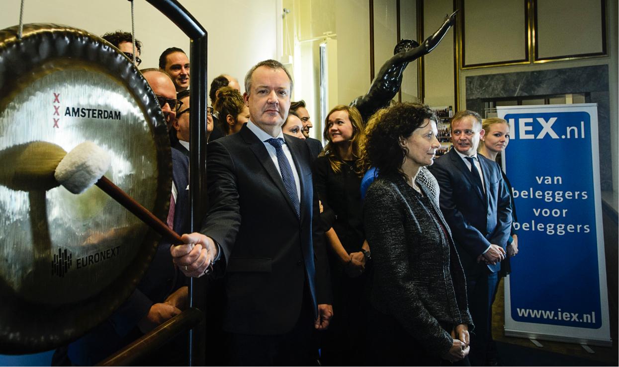 Peter van Sommeren slaat de gong bij AEX met personeel op de achtergrond